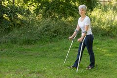 Attractive senior woman walking with crutches stock photo