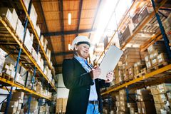 Senior woman warehouse manager or supervisor with tablet, working. Stock Photo