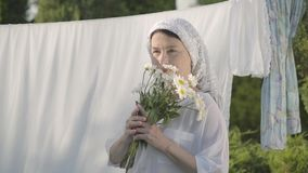 Attractive senior woman with white shawl on her head sniffing daisies looking at camera smiling at the clothesline. Outdoors. Washday. Positive housewife doing stock footage