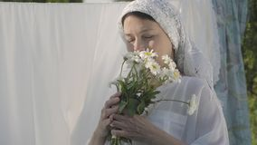 Portrait senior woman with white shawl on her head sniffing daisies looking at camera near the clothesline outdoors. Attractive senior woman with white shawl on stock footage