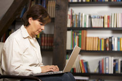 Attractive senior woman working on  laptop. Modern senior woman sitting in front of bookshelf and working on laptop, profile view Royalty Free Stock Photo
