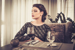 Attractive sensual young lady with glass of wine in restaurant Stock Photos