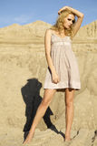 Attractive and sensuality woman dancing in the desert. Fashionable young attractive and sensuality blonde woman in brown dress  on the desert Royalty Free Stock Images