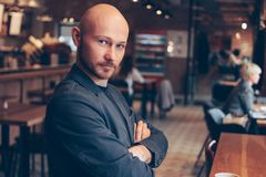 Attractive serious bald man looking at camera in cafe stock images