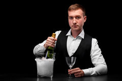 A barman with a bottle of champagne and an empty glass in his hands on a black background. Restaurant service concept. Royalty Free Stock Images