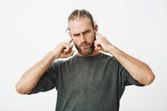 Attractive serious bearded guy with angry expression trying to concentrate while neighbours in next apartment partying. With loud music Royalty Free Stock Photography