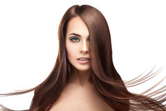 Attractive serious brunette lady with makeup and perfect straigh. T hairstyle on white background in studio Stock Image