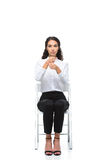 Attractive serious woman gesturing signed language while sitting on chair Royalty Free Stock Images