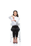 Attractive serious woman gesturing signed language while sitting on chair Royalty Free Stock Photo