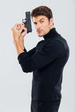 Attractive serious young man standing and holding a gun Stock Photos