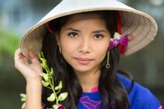 Attractive serious young Vietnamese woman. In a conical straw hat with a fresh flower in her hair, looking at the camera with her hand to the brim stock images