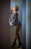 Attractive sexy blonde with blue checkered shirt applying makeup in the bathroom window. Full length portrait of sensual blonde Stock Photo