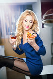 Attractive blonde female with bright blue blouse and black stockings posing smiling eating a pizza slice and holding a glass Royalty Free Stock Photos
