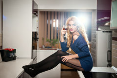 Attractive sexy blonde female with bright blue blouse and black stockings posing smiling holding a glass with red wine Royalty Free Stock Images