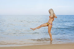 Attractive and sexy blonde girl on the beach. Smiling woman in suimsuit standing on beach, sunny summer day Royalty Free Stock Photography