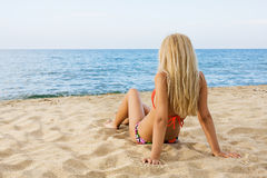 Attractive and sexy blonde girl on the beach. Smiling woman in suimsuit standing on beach, sunny summer day Stock Images