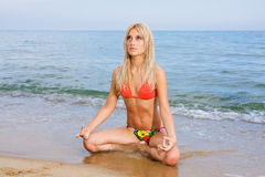 Attractive and sexy blonde girl on the beach. Smiling woman in suimsuit standing on beach, sunny summer day Royalty Free Stock Photos