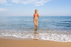 Attractive and sexy blonde girl on the beach. Smiling woman in suimsuit standing on beach, sunny summer day Stock Photography