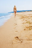 Attractive and sexy blonde girl on the beach. Smiling woman in suimsuit standing on beach, sunny summer day Stock Photos