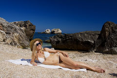 Attractive and sexy blonde girl on the beach. Smiling woman in suimsuit standing on beach, sunny summer day Royalty Free Stock Photo