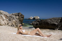 Attractive and sexy blonde girl on the beach. Smiling woman in suimsuit standing on beach, sunny summer day Stock Photo