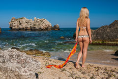 Attractive and sexy blonde girl on the beach. Smiling woman in suimsuit standing on beach, sunny summer day Royalty Free Stock Image