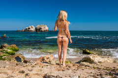Attractive and sexy blonde girl on the beach. Smiling woman in suimsuit standing on beach, sunny summer day Royalty Free Stock Images