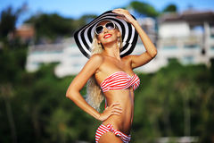 Attractive sexy blonde girl in swimsuit hat and sunglasses Stock Photography