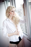 Attractive blonde with white shirt looking on the window in daylight. Portrait of sensual long fair hair woman wearing blouse Royalty Free Stock Images