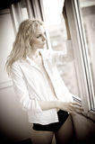 Attractive blonde with white shirt looking on the window in daylight. Portrait of sensual long fair hair woman wearing blouse Royalty Free Stock Photo