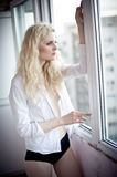Attractive blonde with white shirt looking on the window in daylight. Portrait of sensual long fair hair woman wearing blouse Royalty Free Stock Photos