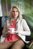Attractive blonde in white sweater over pink blouse holding a cup of coffee. Portrait of sensual woman sitting Stock Images
