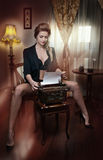 Attractive sexy blonde woman with black bra posing provocatively sitting on chair typing on typewriter. Beautiful woman Stock Photography