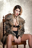 Attractive and sexy blonde woman with black lingerie and fur coat posing provocatively sitting on chair, gray background. Sensual Stock Photo