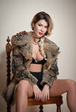 Attractive and sexy blonde woman with black lingerie and fur coat posing provocatively sitting on chair, gray background. Sensual Stock Image