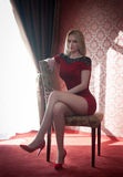 Attractive and sexy blonde woman with red short tight fit dress posing sitting on chair near a window. Sensual female Stock Photography