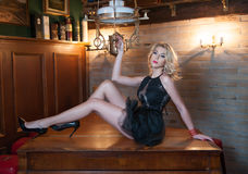 Attractive and sexy blonde woman with short black lace dress posing provocatively lying on wooden table in vintage kitchen Royalty Free Stock Image