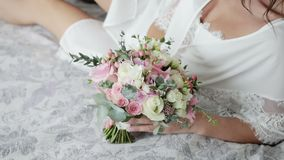 An attractive, sexy bride in a boudoir lies on the bed and touches a beautiful wedding bouquet of pink and white roses. Steadicam shot of an attractive, sexy stock footage