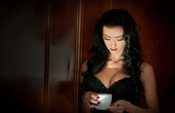 Attractive brunette with black bra holding a white cup of coffee. Portrait of sensual woman in classic boudoir scene. Woman with long enjoying a coffee in semi stock image