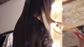 Attractive sexy brunette with long hair standing in front of a mirror. trying on evening dress and admiring herself in. The reflection. gently stroking her body stock footage