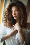 Attractive sexy brunette in white blouse posing provocatively in window frame. Portrait of sensual woman in classic boudoir scene. Stock Images