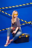 Attractive sexy builder girl in chechered shirt, jeans and glass. Isolated on blue, attractive blonde caucasian builder girl in chechered shirt, jeans and yellow Stock Photos