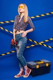 Attractive sexy builder girl in chechered shirt, jeans and glass. Isolated on blue, attractive blonde caucasian builder girl in chechered shirt, jeans and yellow Royalty Free Stock Image