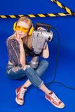 Attractive sexy builder girl in chechered shirt, jeans and glass. Isolated on blue, attractive blonde caucasian builder girl in chechered shirt, jeans and yellow Stock Photography