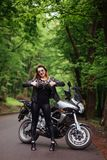An attractive sexy girl on a sports motorbike posing outside Stock Image