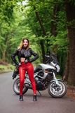 An attractive sexy girl on a sports motorbike posing outside Stock Photography