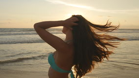 Attractive sexy girl with long hair posing on the ocean shore at sunrise. Beautiful young woman in bikini standing near Stock Images