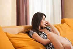 Attractive sexy girl sitting on sofa in a room Royalty Free Stock Images