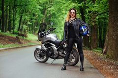 An attractive girl on a sports motorbike posing outside royalty free stock photos