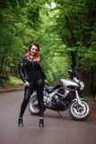 An attractive girl on a sports motorbike posing outside stock photos